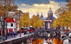 Amsterdam, Netherlands. Autumn sunset in Red-light district. View at Church saint Nicholas above bridge canal with boats. Embankment street lamp and yellow trees Evening streets landscape.
