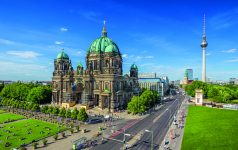 Aerial view of Berlin Cathedral at Lustgarten park with famous TV tower in the background on a sunny day with blue sky and clouds in summer, Berlin Mitte district, Germany.