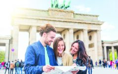 Multiracial group of friends visiting the city of Berlin. Two women and a man looking at a map with Brandenburg Gate on background. Lifestyle, friendship and tourism concepts with real people models.