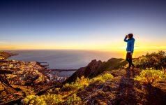 Young female traveler in blue jacket enjoying landscape view on Santa Cruz city on La Palma island in the morning